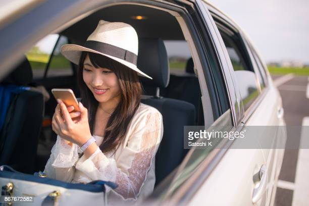 Young woman sitting on passenger seat and watching screen on smart phone