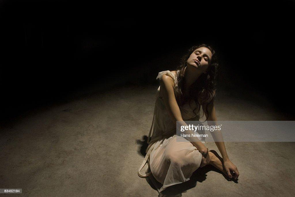 Young woman sitting on pavement : Stock Photo
