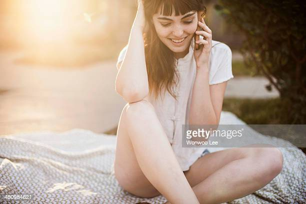 Young woman sitting on picnic blanket talking on cellphone