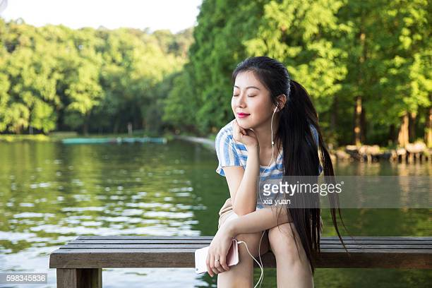young woman sitting on pier against lake,smiling with eyes closed - chinese music stock pictures, royalty-free photos & images