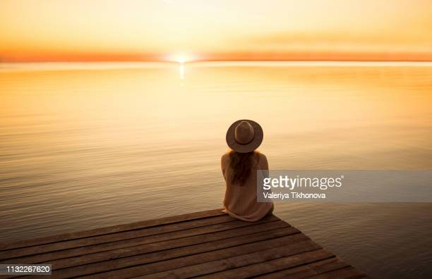 young woman sitting on pier at sunset - pier stock pictures, royalty-free photos & images