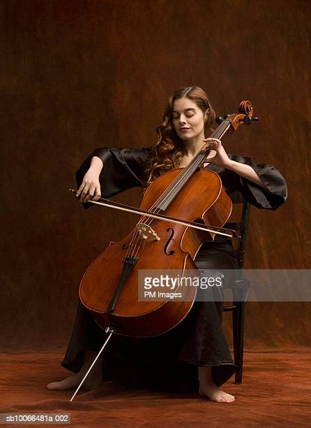 Young woman sitting on playing cello