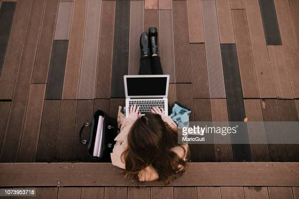 young woman sitting on public park with laptop - the internet stock pictures, royalty-free photos & images