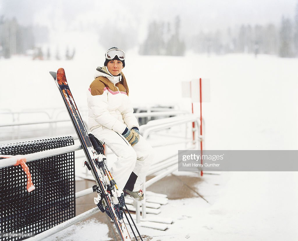 Young woman sitting on railings with ski poles, portrait : Stockfoto