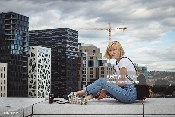 young woman sitting on retaining wall against cityscape - oslo stock pictures, royalty-free photos & images