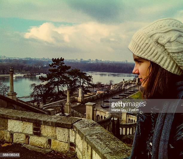 young woman sitting on retaining wall against sky - marija mauer stock-fotos und bilder