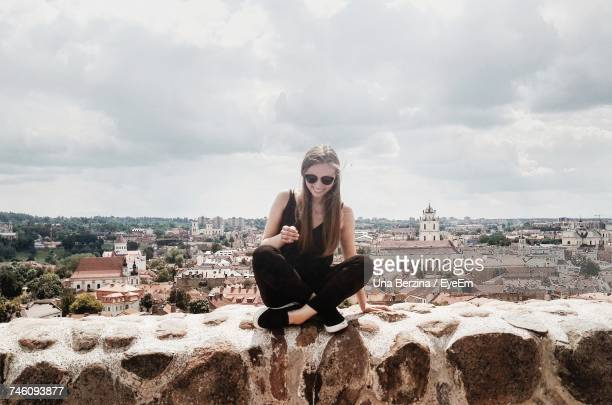 Young Woman Sitting On Retaining Wall At Vilnius Old Town Against Sky