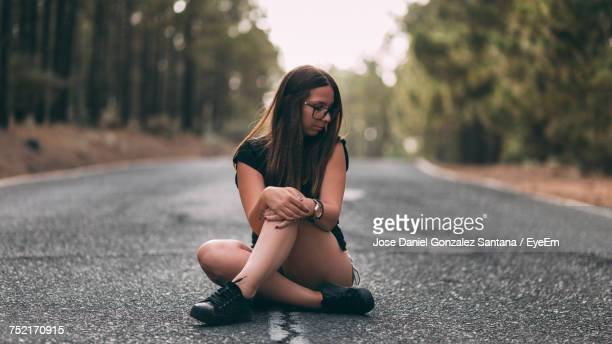 Young Woman Sitting On Road Against Trees