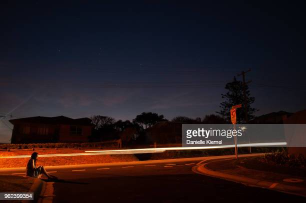 Young woman sitting on road at night, long exposure