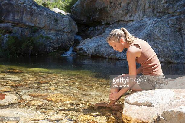 Young woman sitting on rock and bathing in stream