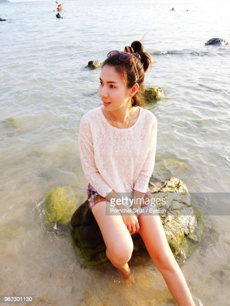 Young Woman Sitting On Rock At Beach
