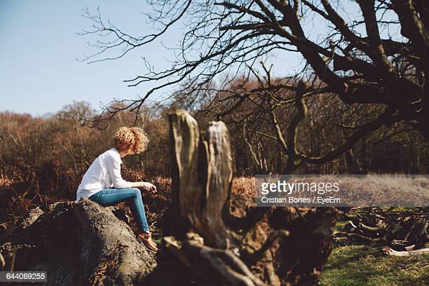 young woman sitting on rock at richmond park - bortes cristian stock photos and pictures