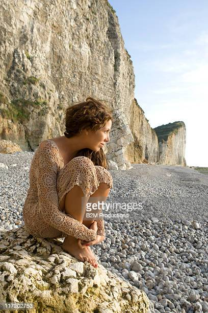 Young woman sitting on rock hugging knees