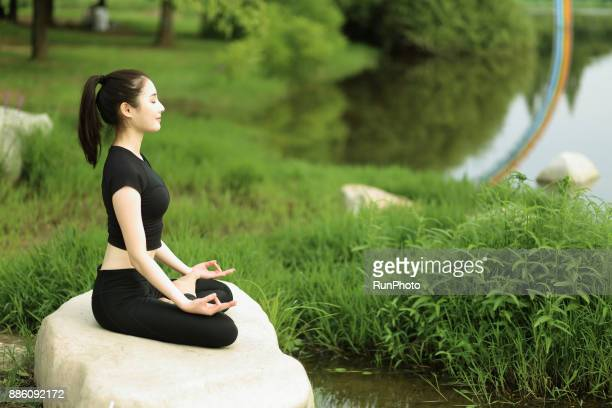 Young woman sitting on rock in the park, meditating