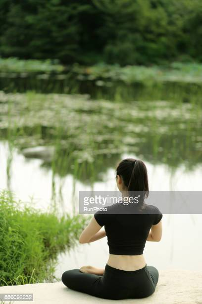 young woman sitting on rock in the park, meditating - 後ろで束ねた髪 ストックフォトと画像