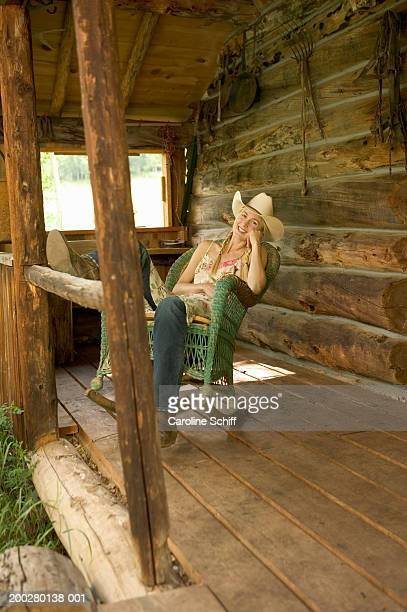 young woman sitting on rocking chair on porch of log cabin, portrait - cowgirl hairstyles stock photos and pictures