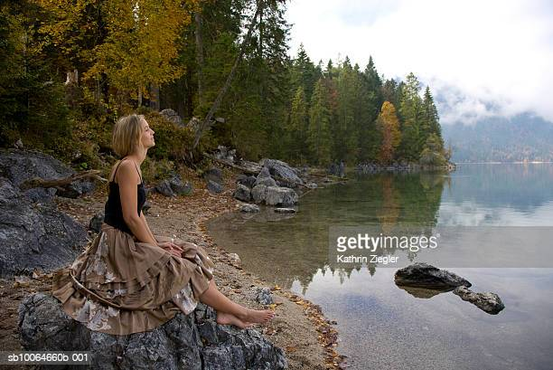 Young woman sitting on rocks at lakeside, side view