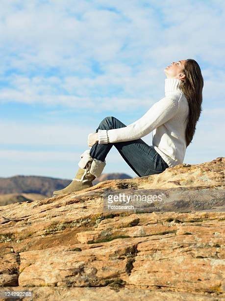 Young woman sitting on rocky hill, low angle view