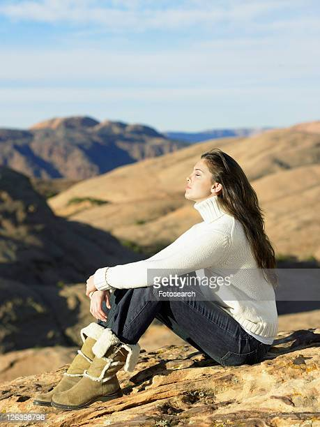Young woman sitting on rocky hill