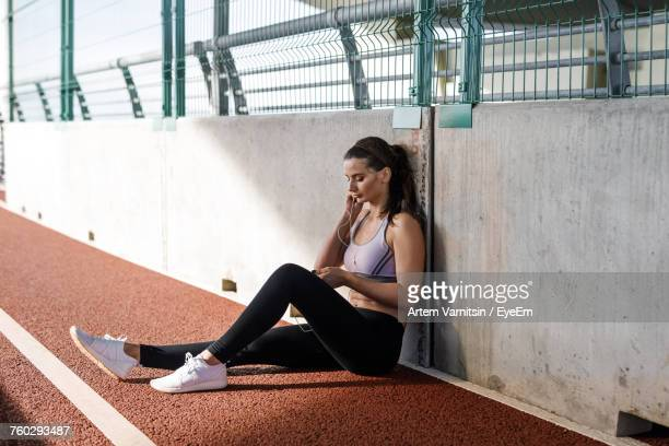 young woman sitting on running track - track and field stadium stock pictures, royalty-free photos & images
