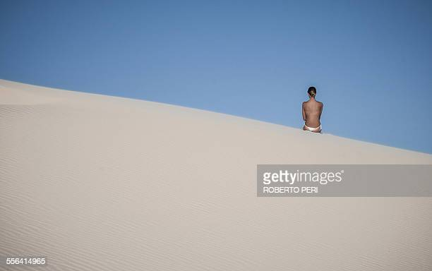 Young woman sitting on sand dune against clear blue sky
