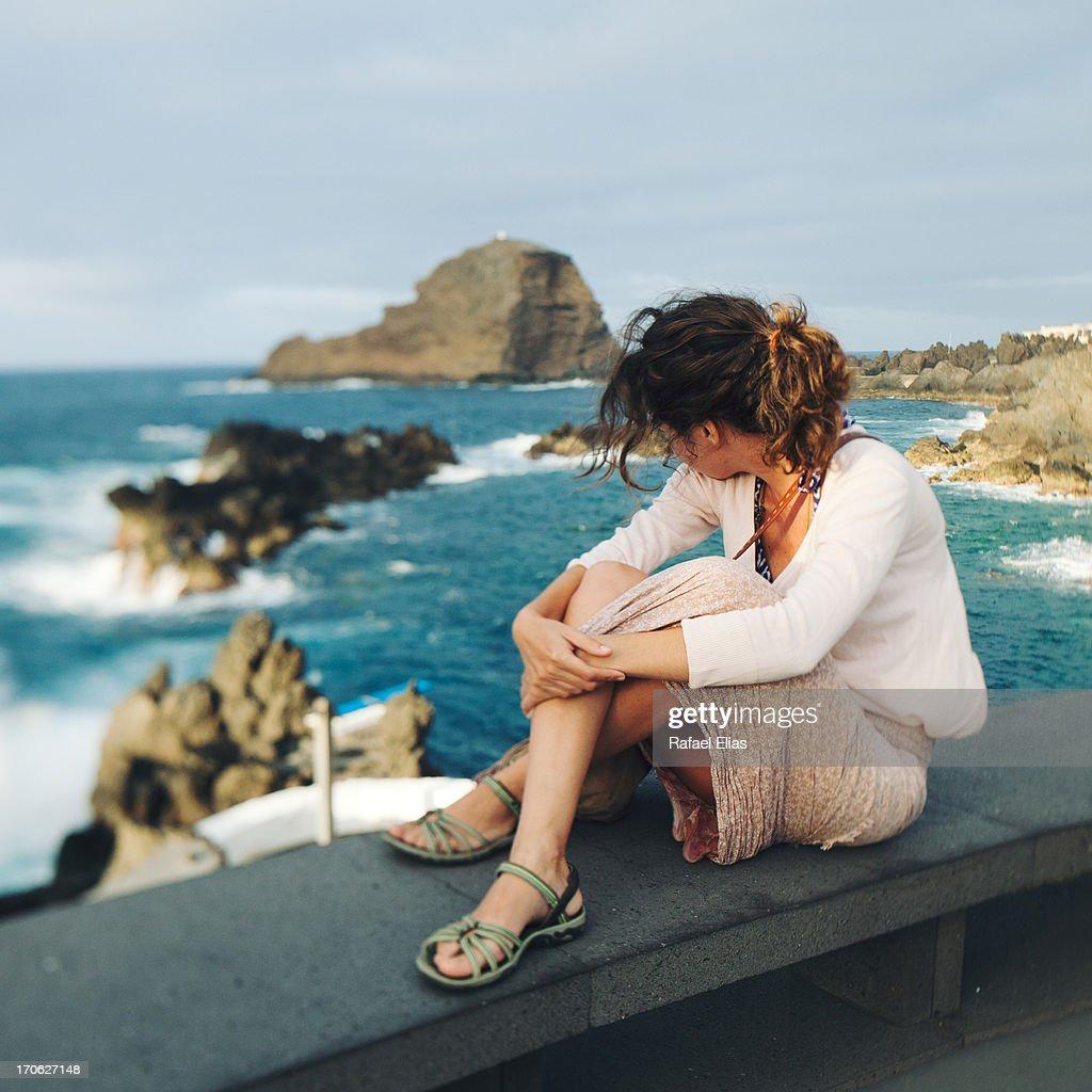 Young woman sitting on seaside breakwater : Stock Photo