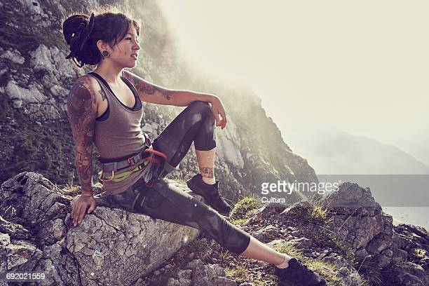 Young woman sitting on side of mountain, looking at view, Innsbruck, Tyrol, Austria