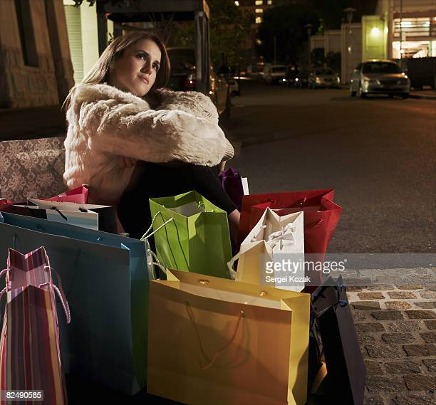 Young woman sitting on sidewalk with shopping outs