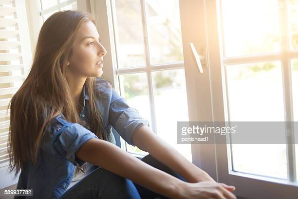 Young woman sitting on sill and looking through window