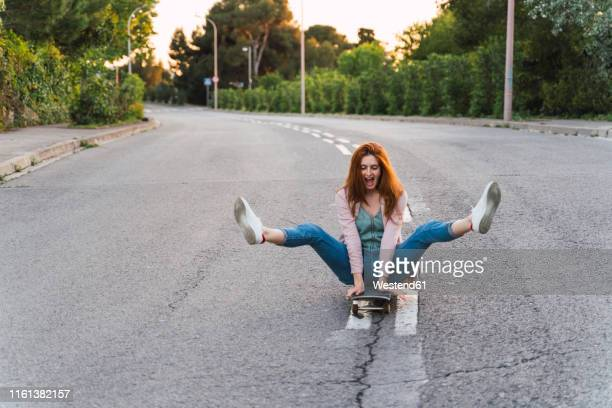 young woman sitting on skateboard and lifting her legs - redhead stock pictures, royalty-free photos & images
