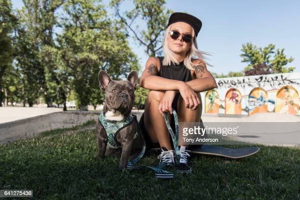 Young woman sitting on skateboard at skatepark with her dog