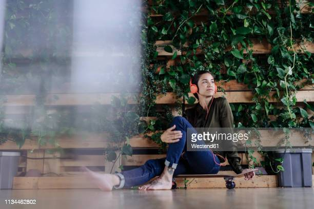 young woman sitting on skateboard at wall with climbing plants listening to music - questions environnementales photos et images de collection