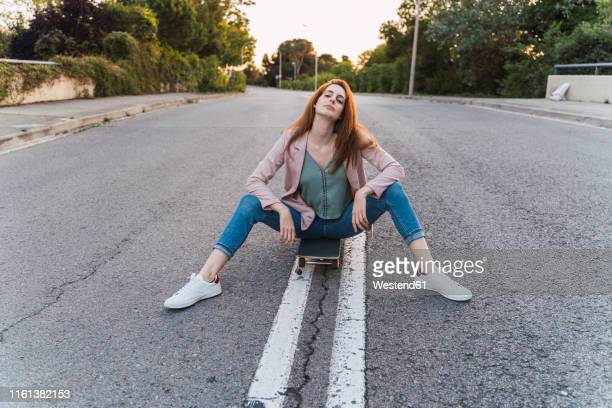young woman sitting on skateboard - legs apart stock pictures, royalty-free photos & images