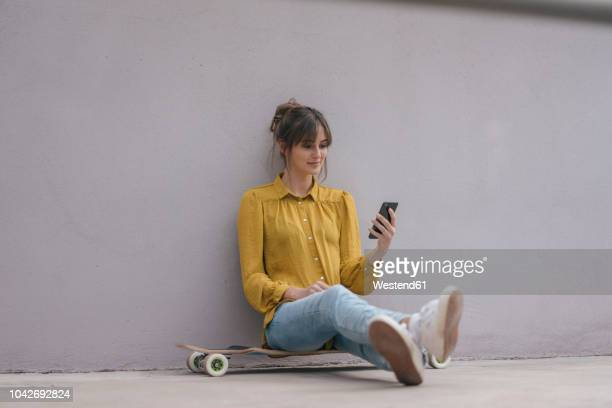 young woman sitting on skateboard, using smartphone - 可動性 ストックフォトと画像