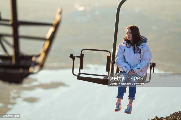 Young Woman Sitting On Ski Lift Over Snowy Mountain