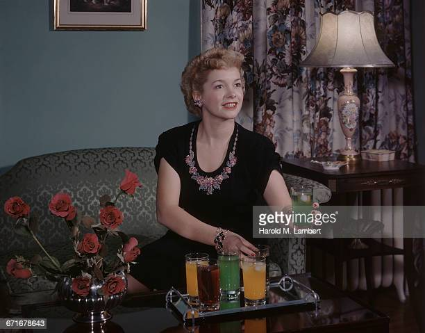 young woman sitting on sofa and serving juice  - {{relatedsearchurl(carousel.phrase)}} imagens e fotografias de stock