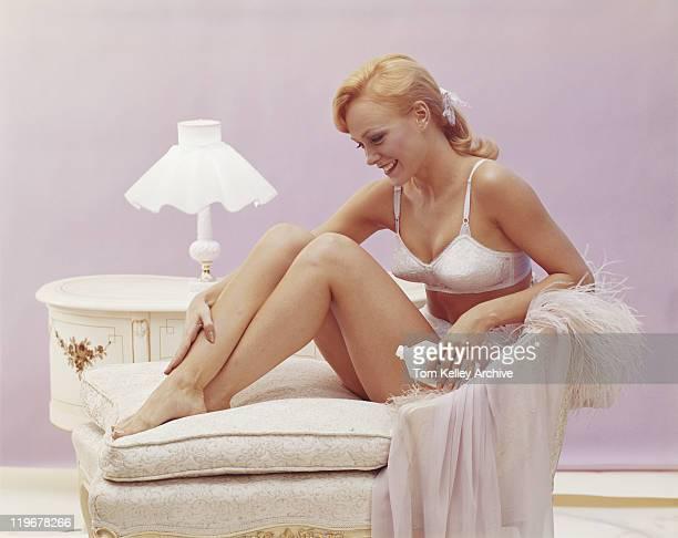 座る若い女性のソファー、笑顔 moisturiser 適用 - 1966年 ストックフォトと画像