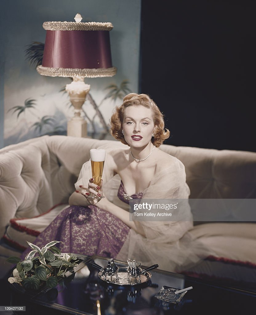 Young woman sitting on sofa holding beer glass, smiling, portrait : Stock Photo