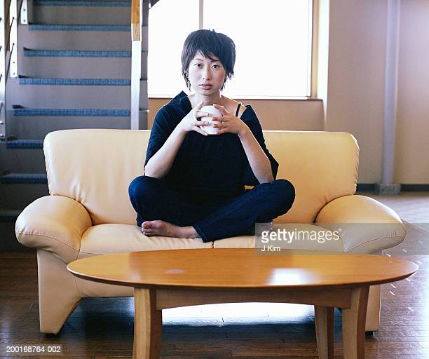 Young woman sitting on sofa, holding coffee cup, portrait