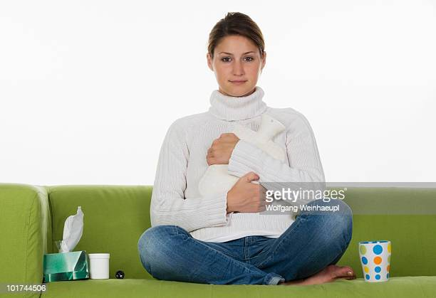 Young woman sitting on sofa, holding hot-water bottle