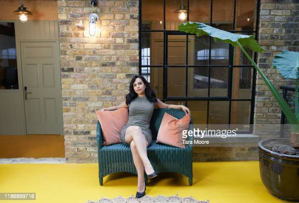 young woman sitting on sofa in open plan office - chair stock pictures, royalty-free photos & images