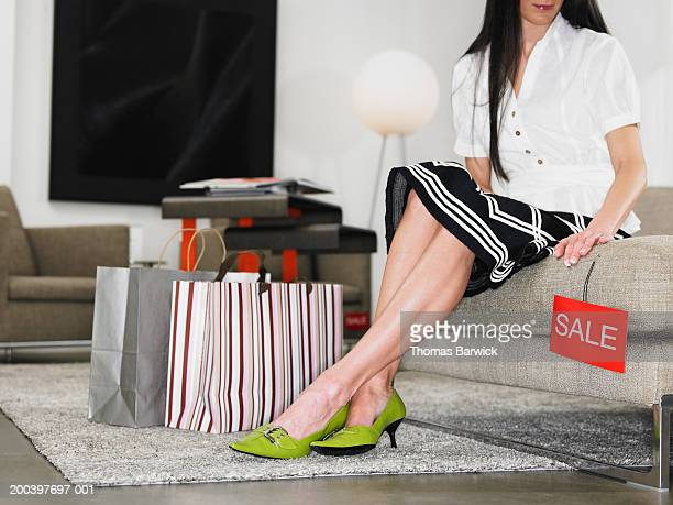 Young woman sitting on sofa in retail store, low section