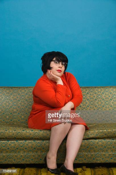 Young woman sitting on sofa leaning chin in hand