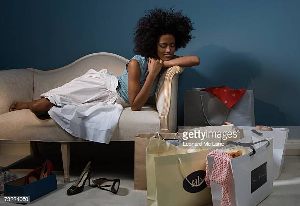 Young woman sitting on sofa, looking at shopping bags on floor