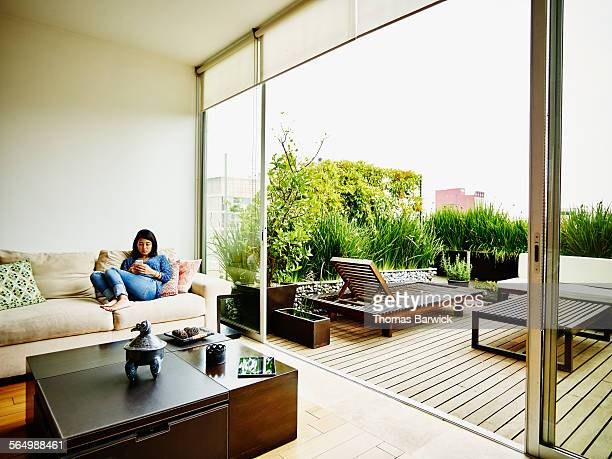 young woman sitting on sofa looking at smartphone - patio stock pictures, royalty-free photos & images
