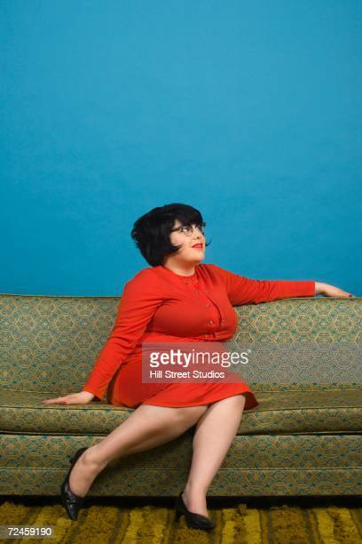 Young woman sitting on sofa looking to the side