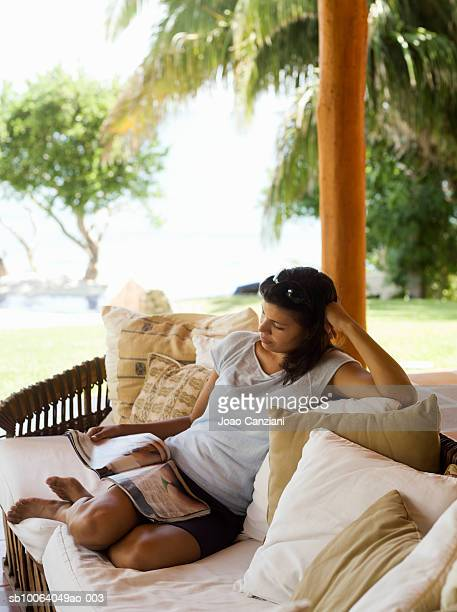 Young woman sitting on sofa outdoors, reading magazine