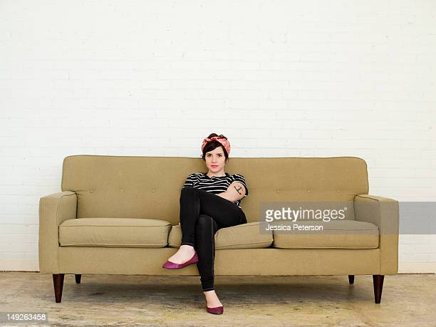 young woman sitting on sofa - sitting fotografías e imágenes de stock