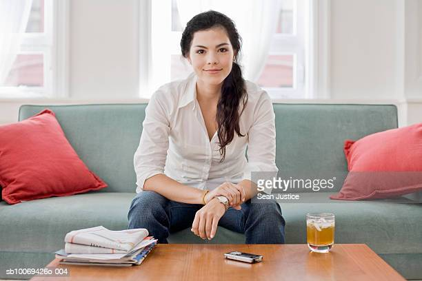 young woman sitting on sofa, portrait - hair back stock pictures, royalty-free photos & images