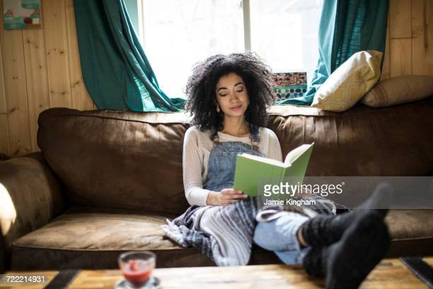 Young woman sitting on sofa, reading book